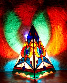 The Harmonic Convergence Pyramid Lamp glows its brilliant design on surrounding walls.